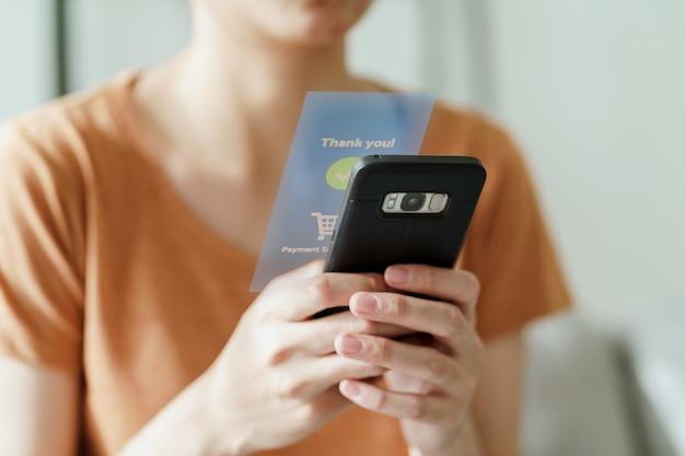 Giovane donna che utilizza lo smartphone per lo shopping online, l'internet banking, l'e-commerce, spendere soldi, lavorare da casa concept