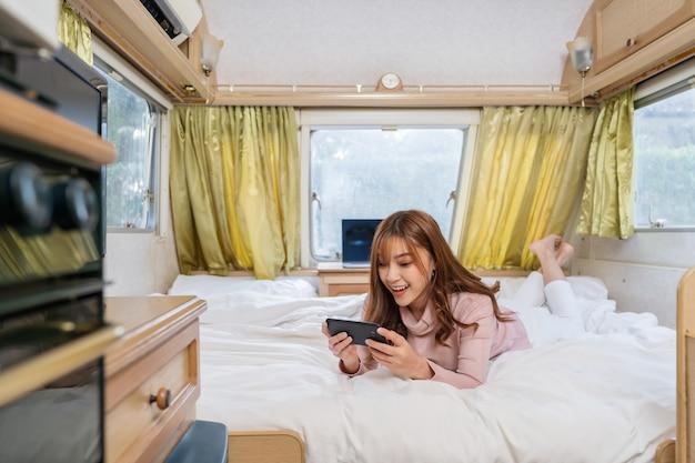 Giovane donna utilizza lo smartphone sul letto di un camper rv van motorhome