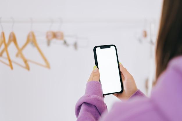 Giovane donna nell'utilizzo di smartphone con mock-up di schermo bianco nella stanza guardaroba bianco con cremagliera del pavimento.