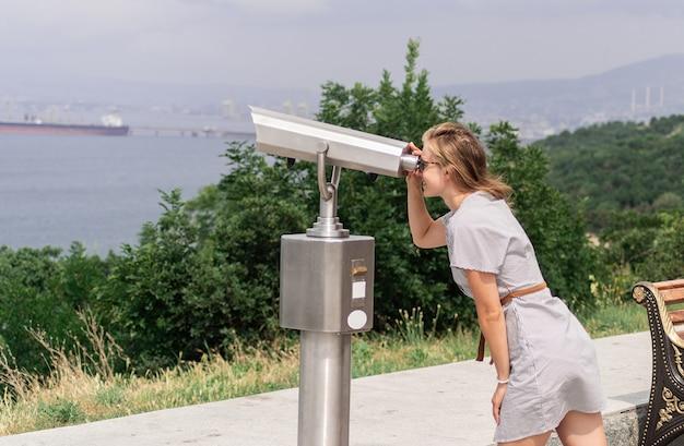 Giovane donna che utilizza un binocolo fisso in una calda giornata estiva