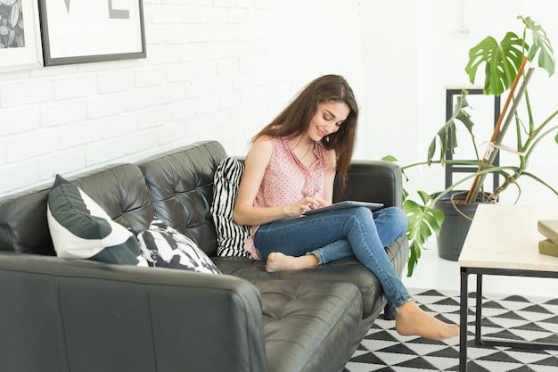 Giovane donna che utilizza tablet a casa