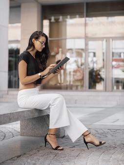 Giovane donna che utilizza tablet pc in strada della città. signora di moda affari alla moda in bicchieri che lavorano all'aperto