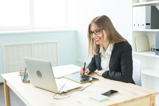 Giovane donna utilizzando tablet e guardando in laptop