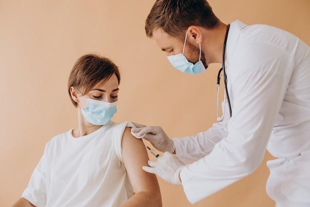 Giovane donna che vaccina in ospedale