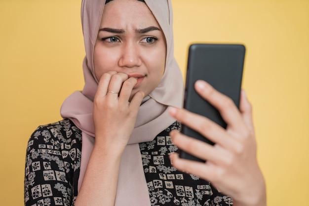 Giovane donna in velo scioccata e preoccupata mentre guarda lo schermo del telefono cellulare con il gesto del dito morso