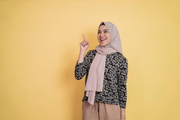 Giovane donna in velo che sorride mentre alza il gesto della mano trovando un'idea con lo spazio