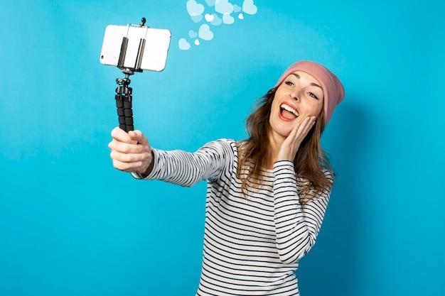 Il video blogger di una giovane donna scatta foto di se stessa al telefono mentre trasmette su una parete blu. storia concettuale, vlog, selfie, blog.