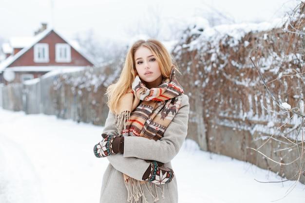 Giovane donna in un cappotto grigio vintage in un'elegante sciarpa di lana in caldi guanti di lana si trova nel paesaggio invernale