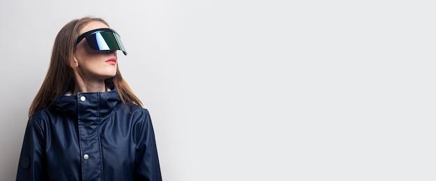 La giovane donna con gli occhiali per realtà virtuale guarda di lato su uno sfondo chiaro. bandiera.