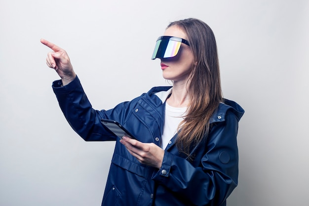 Giovane donna in occhiali per realtà virtuale con un telefono punta il dito di lato su uno sfondo chiaro.