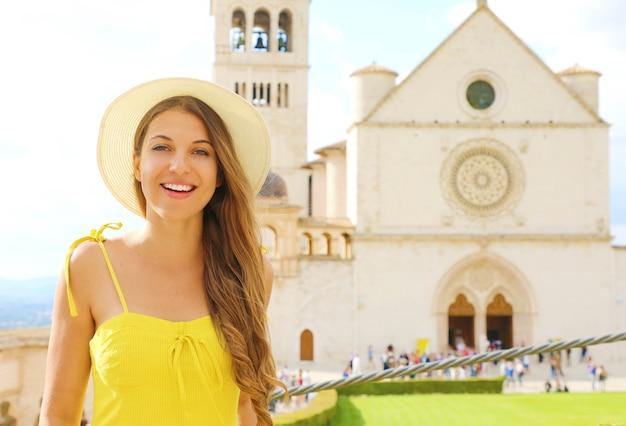Giovane donna che visita la basilica di san francesco d'assisi il giorno pieno di sole