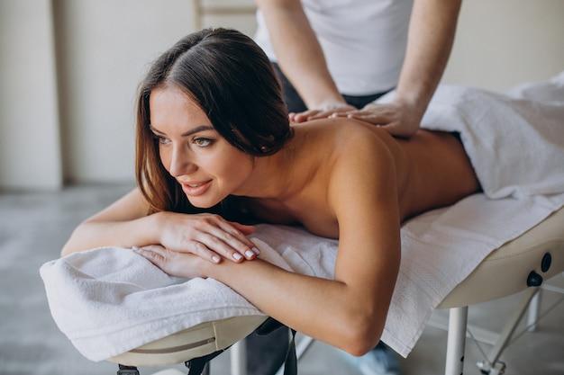 Giovane donna visitando il massaggiatore al centro termale