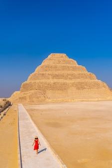 Una giovane donna che visita la piramide a gradini di djoser, saqqara. egitto. la necropoli più importante di menfi. la prima piramide al mondo