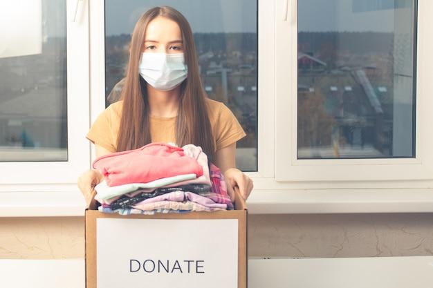 Giovane donna volontaria con una scatola di vestiti per i poveri, gli orfani, i bambini bisognosi e i senzatetto
