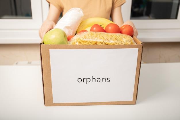 Una giovane donna volontaria con una scatola di prodotti alimentari per gli orfani negli orfanotrofi