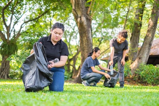 Volontari della giovane donna che raccolgono rifiuti in parco. concetto di protezione ambientale
