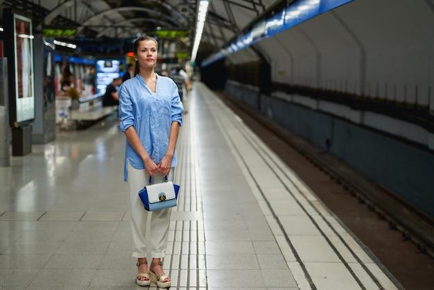 Giovane donna in attesa sul binario di una stazione ferroviaria per l'arrivo del treno. trasporto pubblico.