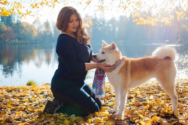 Giovane donna in una passeggiata con il suo cane akita inu di razza