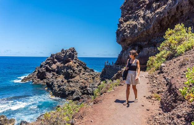 Una giovane donna che cammina lungo il sentiero in estate verso la spiaggia di nogales a est dell'isola di la plama, isole canarie. spagna