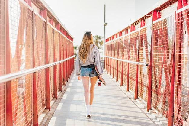 Giovane donna che si allontana su un ponte che tiene un pattino