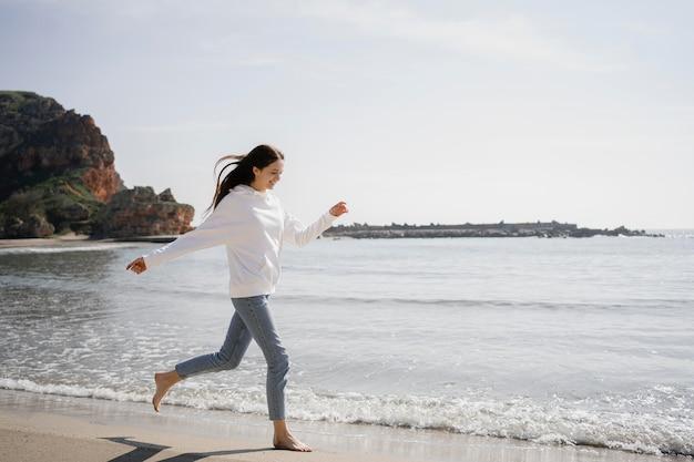 Giovane donna che cammina sulla spiaggia di sabbia