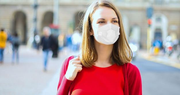Giovane donna che cammina in città in abiti casual, covid o concetto di coronavirus