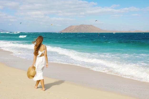 Giovane donna che cammina sulla spiaggia di corralejo, fuerteventura, isole canarie
