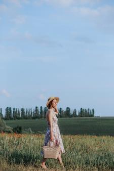 Giovane donna che cammina sul campo di fiori al tramonto sullo sfondo. vista orizzontale con spazio di copia