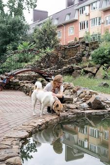 Giovane donna che porta a spasso il suo cane in un parco