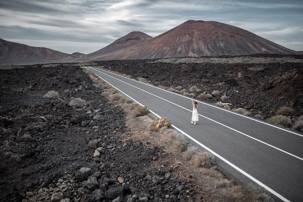 Giovane donna che cammina nel mezzo di una strada solitaria immersa in un oscuro paesaggio di montagna.