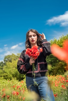 Giovane donna che cammina sul campo di papaveri rossi nel periodo estivo