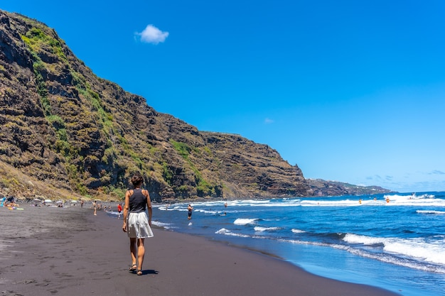 Una giovane donna che cammina in estate in riva al mare a playa de nogales a est dell'isola di la plama, isole canarie. spagna