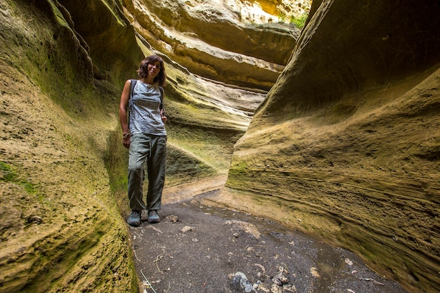 Una giovane donna che cammina attraverso il canyon del parco nazionale di naivasha hell's gate pieno di animali. kenya walking o bike safari