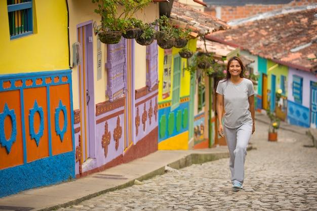 Giovane donna che cammina nel tradizionale villaggio colombiano