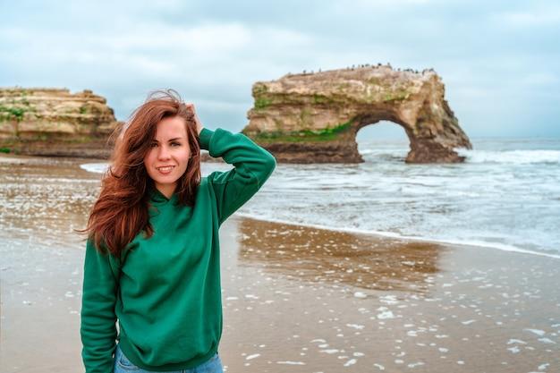 Una giovane donna cammina sulla spiaggia con vista sul ponte naturale a santa cruz california