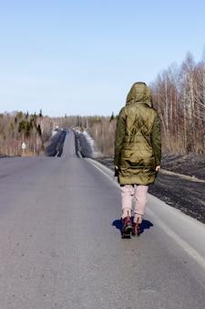 Una giovane donna cammina sul ciglio della strada. strada nella foresta.