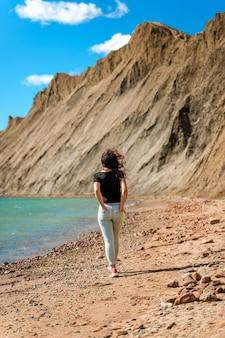 Una giovane donna cammina su una spiaggia deserta a cape chameleon in crimea