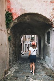 La giovane donna cammina per le strade europee storiche della città vecchia