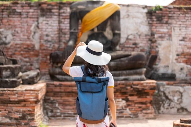 Una giovane donna cammina nel vecchio tempio in phra nakhon si ayutthaya, thailandia in una giornata rilassante.