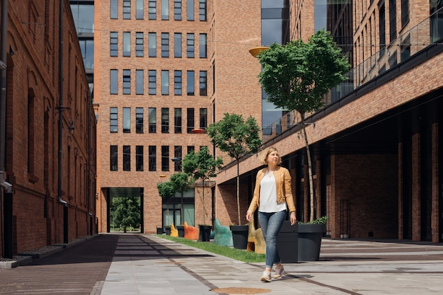 La giovane donna cammina per le strade della città il giorno di primavera. paesaggio urbano . la vita è meravigliosa. turismo e piacere. blog sui viaggi. città europee. la capacità di vivere la vita piena.