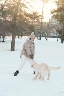 Giovane donna in abiti caldi che cammina fuori insieme al suo cane