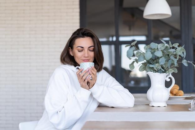 Giovane donna in una calda felpa bianca a casa in cucina, inizia la sua giornata con una tazza di caffè