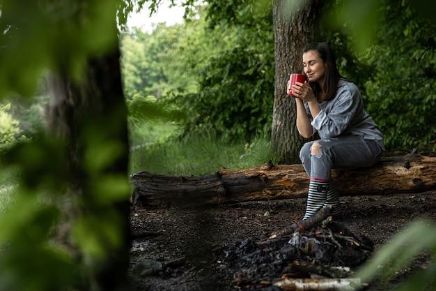Una giovane donna si scalda vicino a un fuoco spento con una tazza di bevanda calda nella foresta tra gli alberi