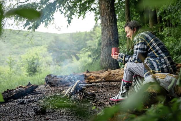 Una giovane donna si scalda vicino a un fuoco spento con una tazza di bevanda calda nella foresta tra gli alberi.