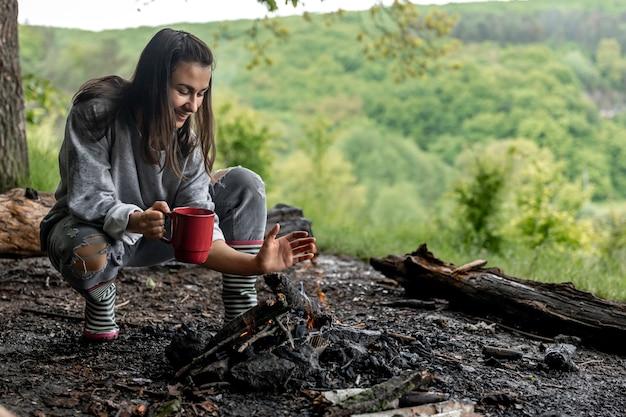 Una giovane donna si scalda vicino al fuoco con una tazza di bevanda calda nella foresta