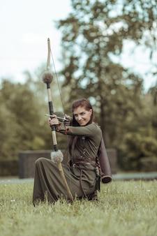 Giovane donna guerriera con un arco siede in una radura e mira da un arco, cacciando in una foresta verde
