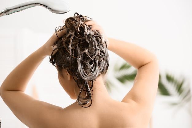 Giovane donna che lava i suoi bei capelli in bagno