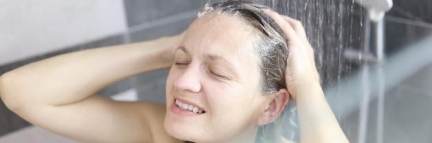 Giovane donna che si lava i capelli con lo shampoo sotto la doccia