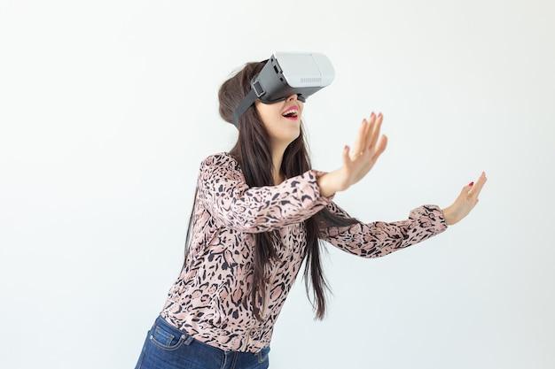 La giovane donna guarda un film con gli occhiali di realtà virtuale in piedi su un muro bianco.