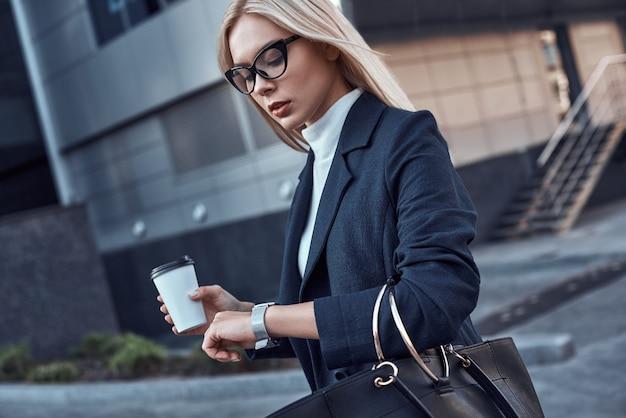 La giovane donna guarda il suo orologio da polso in una delle sue mani il caffè in un'altra borsetta